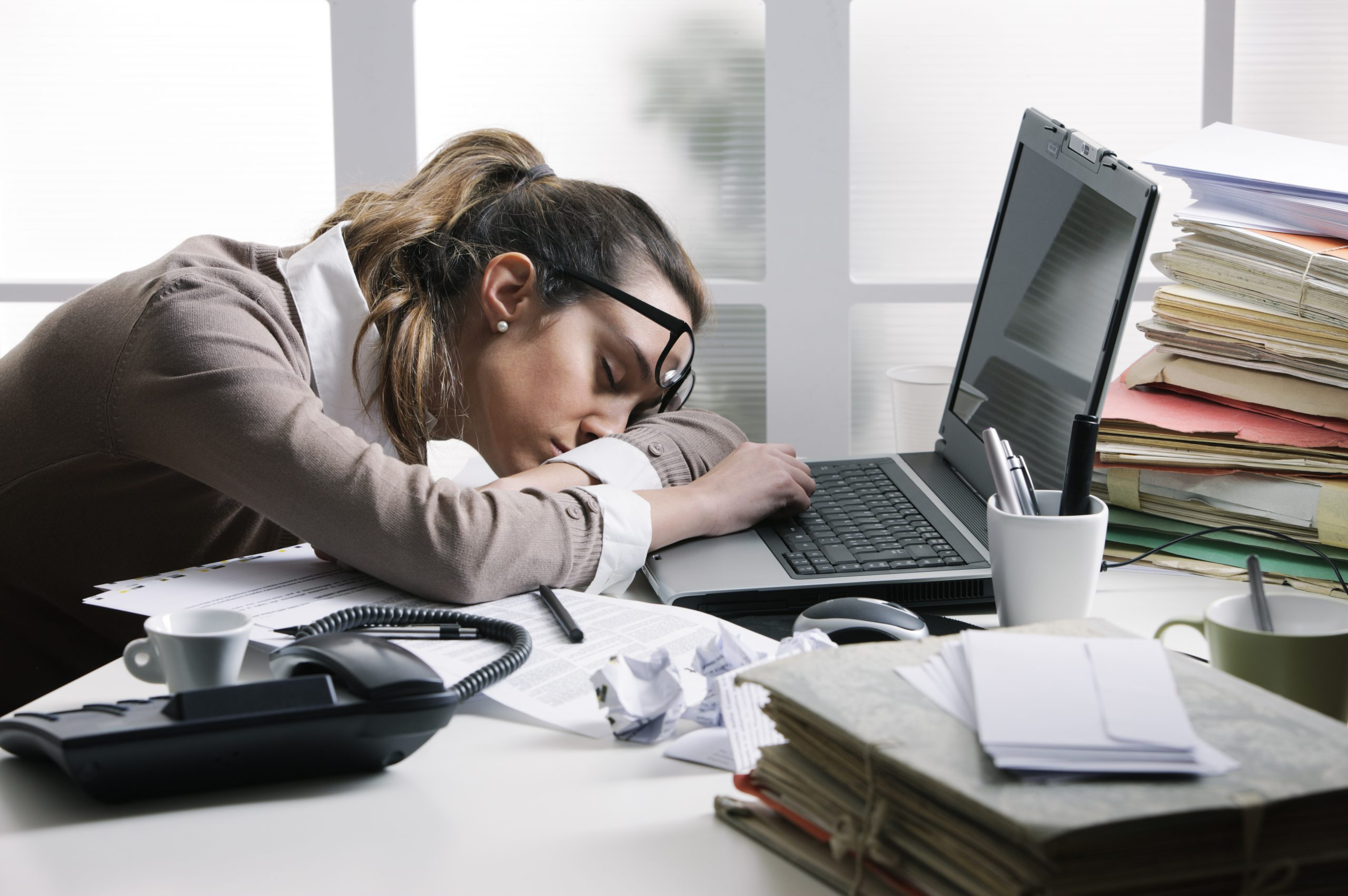 Tired businesswoman sleeping on the desk, in front of the computer screen.